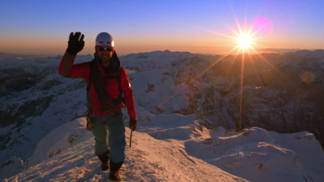 PAN Mountaineers waving as they reach the snowy mountain top at sunset