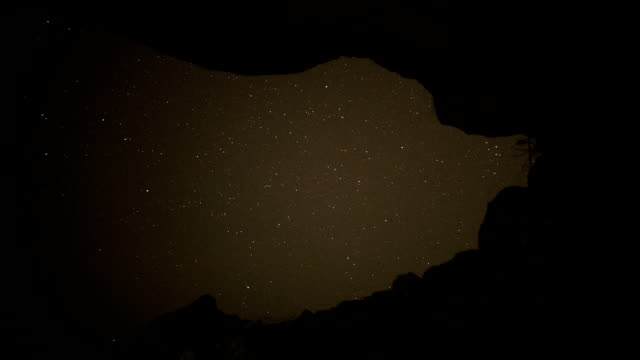 mountainous coastline under night sky time lapse - cave stock videos & royalty-free footage