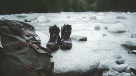 vídeos y material grabado en eventos de stock de paisaje montañoso. cerrar sobre botas y mochila de senderismo - hacer un descanso