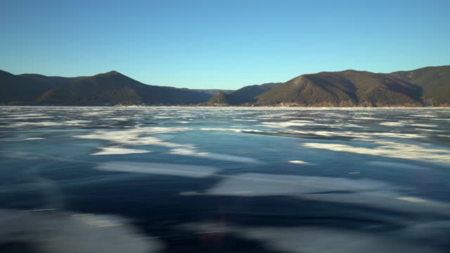 mountains by frozen lake baikal seen from hovercraft against clear blue sky - hovercraft stock videos & royalty-free footage