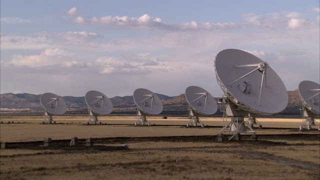 mountains line the horizon behind an array of radio telescopes. available in hd. - telescopio astronomico video stock e b–roll