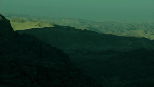 mountains near petra with peaks sunlit and base in shadow, jordan - アラバ砂漠点の映像素材/bロール