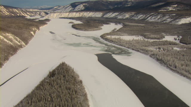 Mountains rise above the frozen Yukon River.