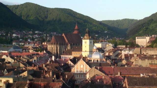 WS ZO Mountains surrounding town with church in center / Sapanta, Maramures, Romania