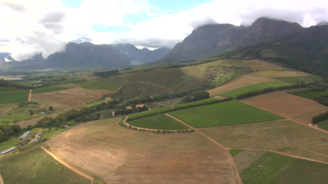 mountains tower beyond a rural valley. available in hd. - paarl stock videos & royalty-free footage