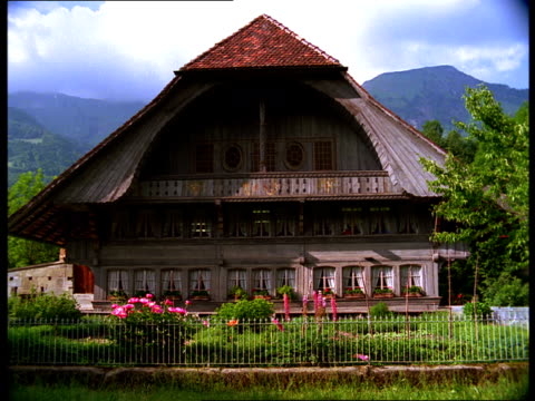 mountains tower over a large chalet. - chalet video stock e b–roll