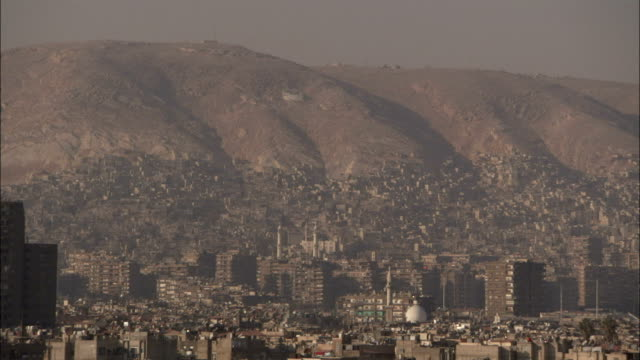 Mountains tower over the city of Damascus. Available in HD.