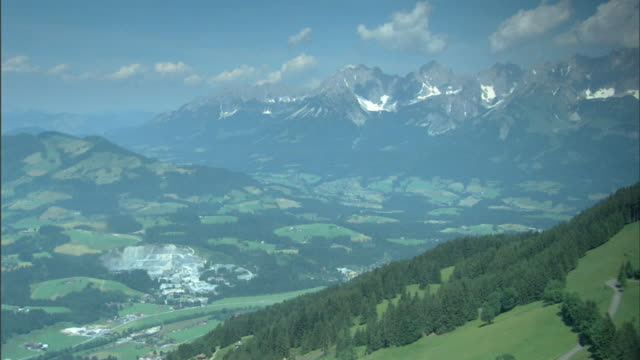 mountains & trees, evergreen trees w/ valley below, higher jagged mountains distant bg. - 北チロル点の映像素材/bロール