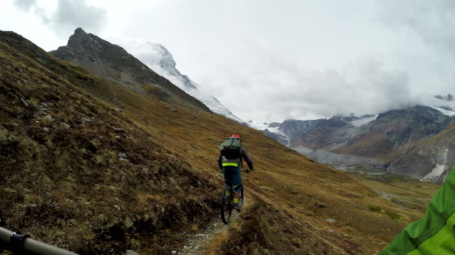 Mountan bikers descend slope with iconic mountain in distance