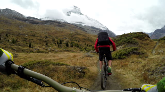 vídeos de stock, filmes e b-roll de mountan bikers descend slope with iconic mountain in distance - mountain bike ciclismo