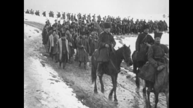 mounted cherkas of the russian caucasus army approach on muddy road; snow lies on both sides of road; infantrymen follow / rear shot infantrymen,... - bildkomposition und technik stock-videos und b-roll-filmmaterial