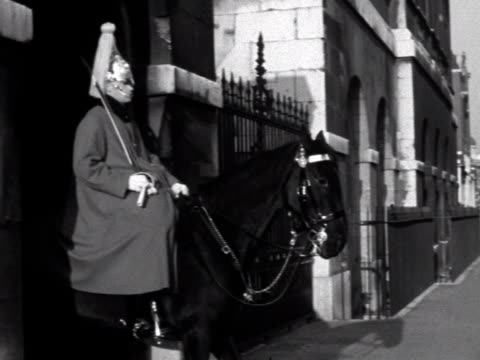 mounted life guard on duty in whitehall. the camera pans right to a man and a young girl walking down the road. 1961. - トラファルガー広場点の映像素材/bロール
