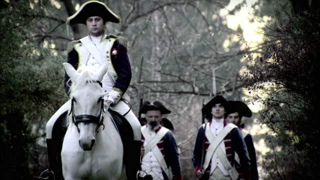 a mounted officer on a white horse leads soldiers in french revolution uniforms. - french revolution stock videos & royalty-free footage