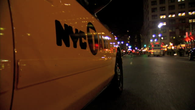 vídeos de stock, filmes e b-roll de ms reflective side of yellow taxi cab nyc taxi logo driving on manhattan streets making turn coming to a stop at red light traffic - táxi