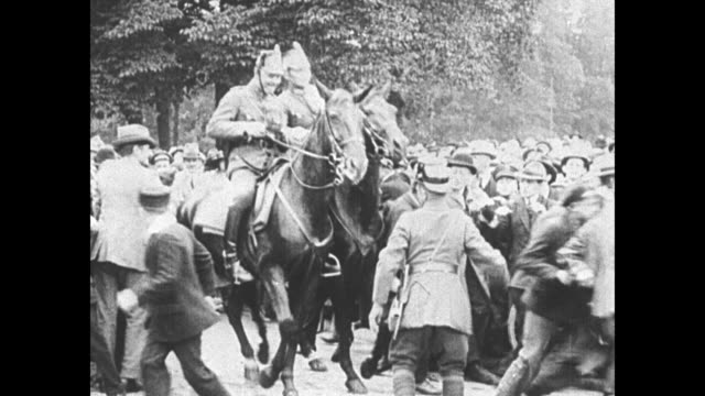 mounted police attempt to quell a civil disorder with horses turning around in a crowd of men and women - 1930 stock-videos und b-roll-filmmaterial