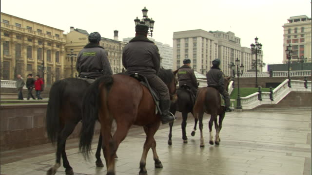 mounted policemen ride past pedestrians in moscow. - russia stock-videos und b-roll-filmmaterial