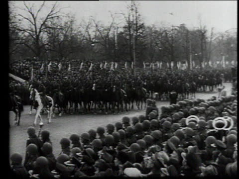 vídeos de stock, filmes e b-roll de mounted unit marching past crowded street lined with soldiers / military leaders on grandstand as soldiers ride past / leader standing before crowd - wehrmacht