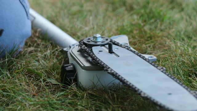 stockvideo's en b-roll-footage met mounting the cover of a gardening chainsaw. - sprocket