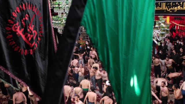 mourners beat themselves as they take part in a religious ceremony during tasoua a day ahead of ashura in the karbalaeiha hussainiyah in southern... - ashura muharram stock videos & royalty-free footage