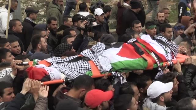 Mourners carry the body of Nimr alJamal who was shot dead September of last year by Israeli forces after carrying out an attack during his funeral on...