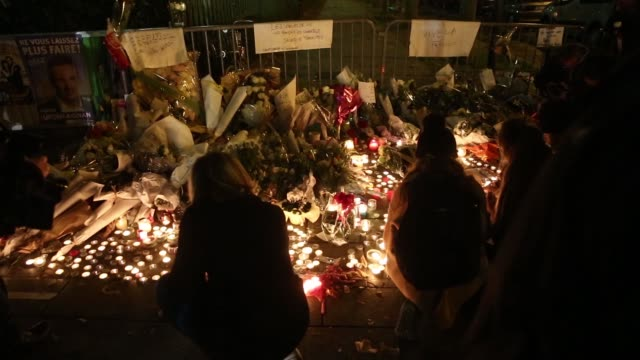 mourners light candles at a memorial site near the bataclan concert hall, where more than 80 people were killed, in paris, france on saturday, nov... - minnesmärke bildbanksvideor och videomaterial från bakom kulisserna