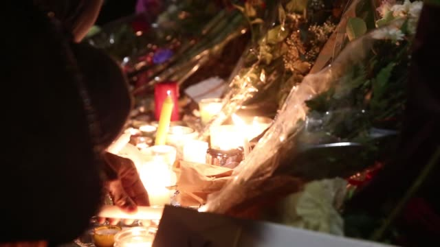mourners light candles at a memorial site near the bataclan concert hall, where more than 80 people were killed, in paris, france on saturday, nov.... - minnesmärke bildbanksvideor och videomaterial från bakom kulisserna