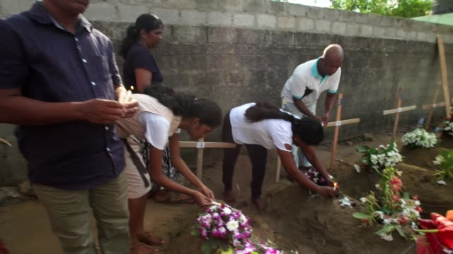 mourners lighting candles at graves in negombo for those killed in the sri lanka terror attacks - sri lanka stock-videos und b-roll-filmmaterial
