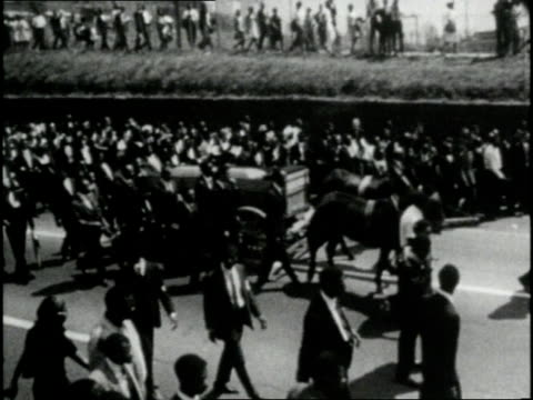mourners march down the street with the rev martin luther king jr's casket during his funeral procession - trauernder stock-videos und b-roll-filmmaterial