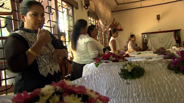 mourners pray around open caskets in negombo of four members of one family killed in the sri lanka terror attacks - sri lanka stock-videos und b-roll-filmmaterial