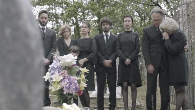 vidéos et rushes de mourners standing around grave - cercueil