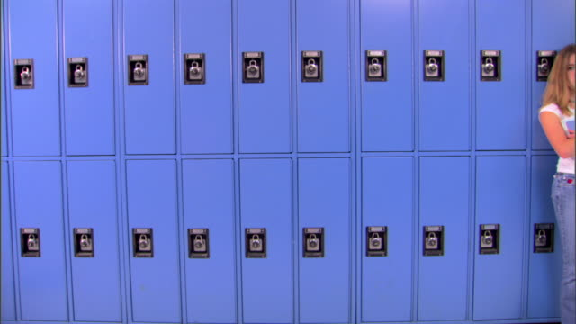 stockvideo's en b-roll-footage met move right across blue school lockers to a lonely girl leaning while holding her books. - lockerkast