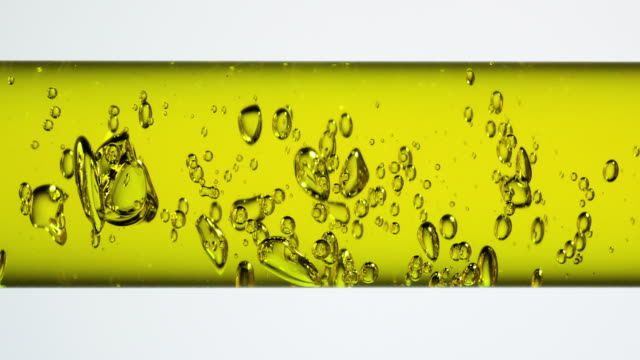 vidéos et rushes de movement of air bubbles in yellow colored water in scientific glassware, holizontal - tube à essai