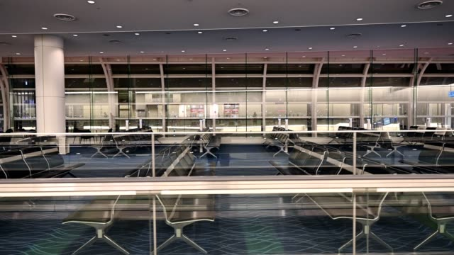 movement on automatic walkway with chairs for passengers in airport - elevated walkway stock videos & royalty-free footage