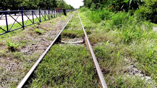 movimento su ferrovia arrugginito con ghiaia e pianta verde in campagna - railway track video stock e b–roll