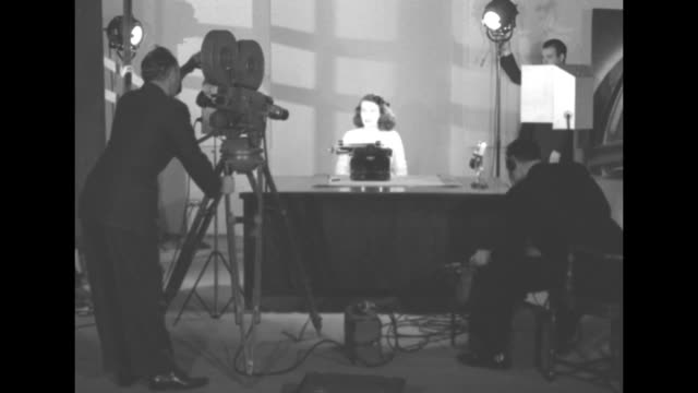 vídeos de stock e filmes b-roll de movie camera, cameraman, lighting and sound technicians surround woman at desk with typewriter / woman types / woman / note: exact year not known;... - sala de imprensa