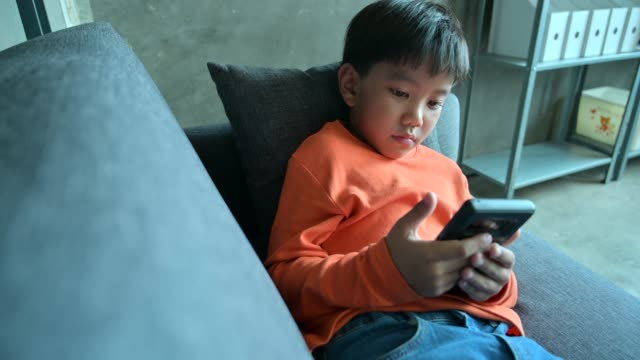 4k movie close up of asian child playing smart phone - digital display stock videos & royalty-free footage