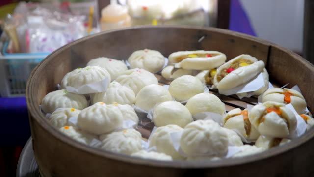 vídeos de stock, filmes e b-roll de 4k filme closeup tiro de recém cozido, pães e bolinhos para venda em chineese andando pela rua, um pequeno restaurante em bangkok, tailândia - bolinho de massa