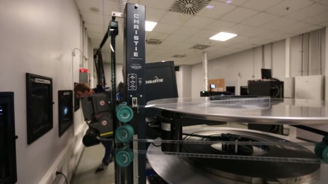 Movie film tape goes through a projector machine in the