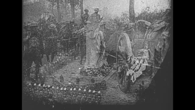 movie footage of british soldiers in combat is superimposed on cenotaph war memorial with crowd around it / scene of cemetery of war dead is... - 戦争記念碑点の映像素材/bロール