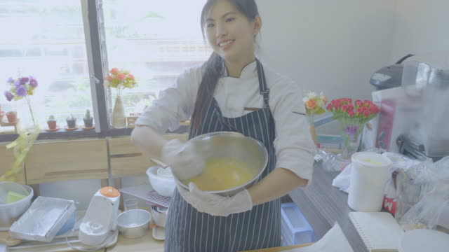 4K Movie of Asian Beautiful female chef cooking and baking brownie cake in the kitchen