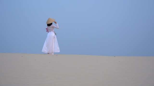 vídeos y material grabado en eventos de stock de 4 película k hermosa vietnamita sostiene rosa lotus caminando en el desierto de dunas de arena blanca, muine, vietnam - posa del loto