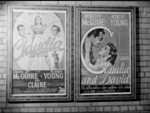 movie posters for 'claudia' 1943 film & sequel 1946 'claudia & david' poster. men shopping at counter, paperback 'pocketbook' claudia books on... - libro in brossura video stock e b–roll