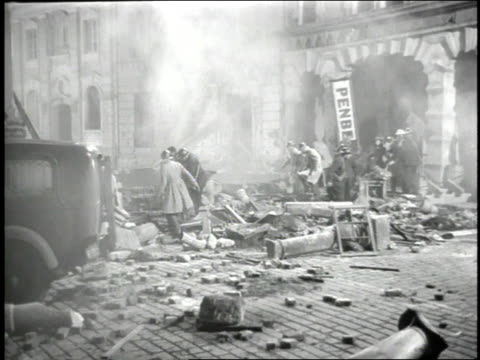 1947 reenactment movie scene of people fighting fires and rescuing injured during an air raid / united kingdom - 空爆点の映像素材/bロール