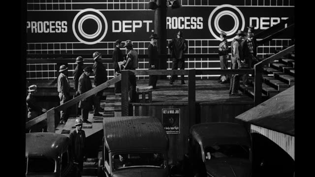 Movie set process plate workers walking up steps behind them a projection screen with workers working on a ship at a shipyard Movie set workers at a...