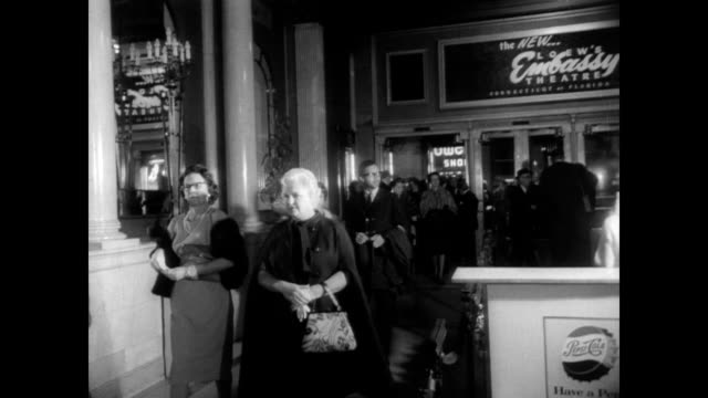 ext movie theater on m street in washington dc / people entering theater / cu movie poster for 'charade' starring cary grant and audrey hepburn /... - generalstaatsanwalt stock-videos und b-roll-filmmaterial