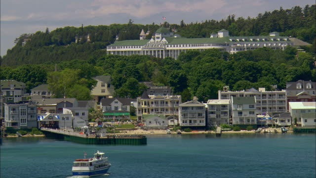 aerial moving across mackinac island waterfront with grand hotel in background as ferry boat approaches dock/ mackinac island, michigan - unknown gender stock videos & royalty-free footage