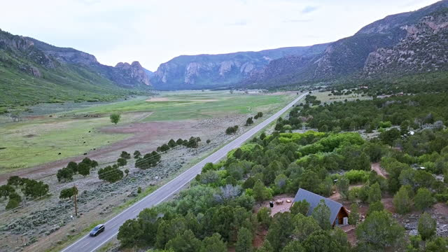 moving aerial shot of a car driving past a modern tiny home with a view of a beautiful canyon and highway 141 in western colorado - modern rock stock videos & royalty-free footage