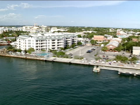 AERIAL Moving along Key West coastline condominiums condos homes resort hotel prime real estate boats docks yachts sailboats public boat ramp...