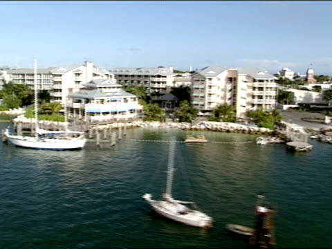 AERIAL Moving along Key West coastline passing public boat ramp condominiums condos homes resorts hotels prime real estate boats docks yachts...