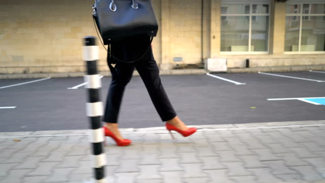 moving camera shot of the feet of one businesswoman walking on sidewalk in the morning - woman accessories stock videos and b-roll footage